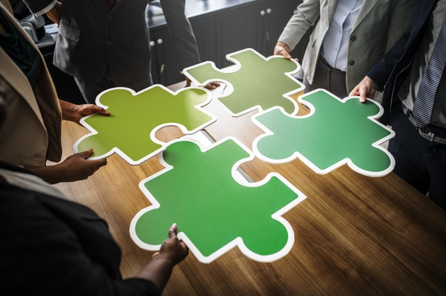executives holding puzzle pieces