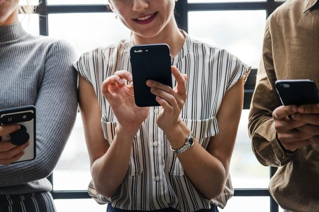 Woman using cellphone in a group