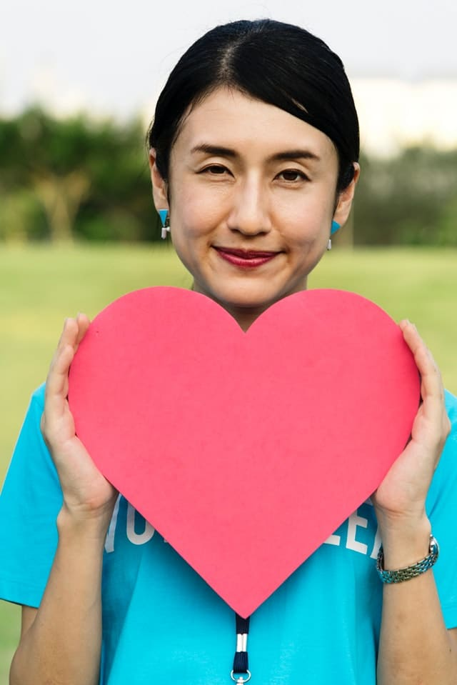 Volunteer holding a cut out heart