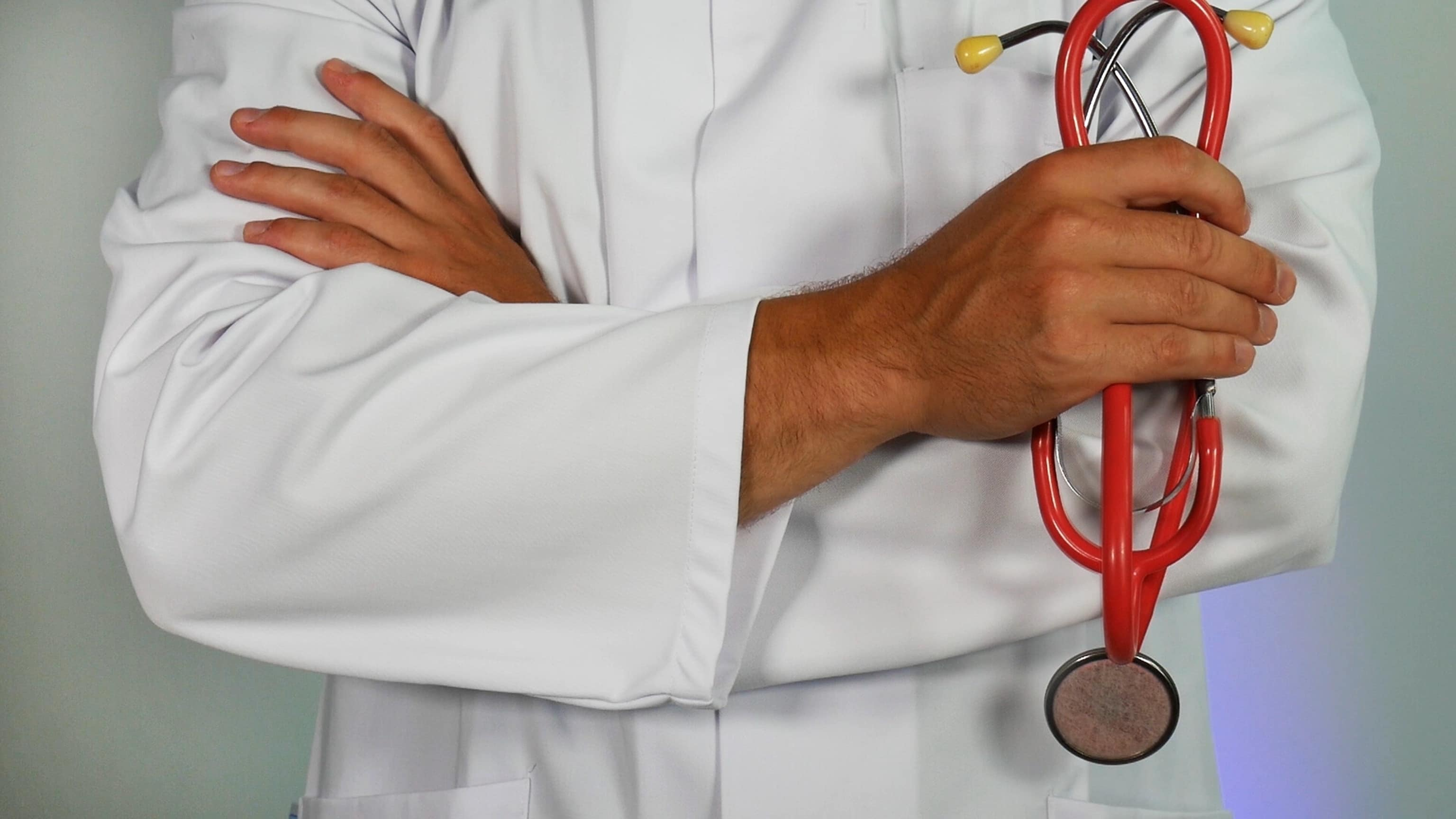 Doctor wearing a white coat holding a stethoscope