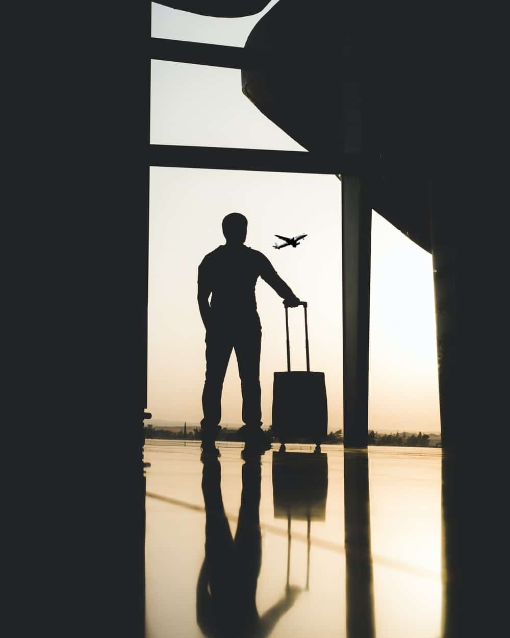 Man stands near airport window with briefcase